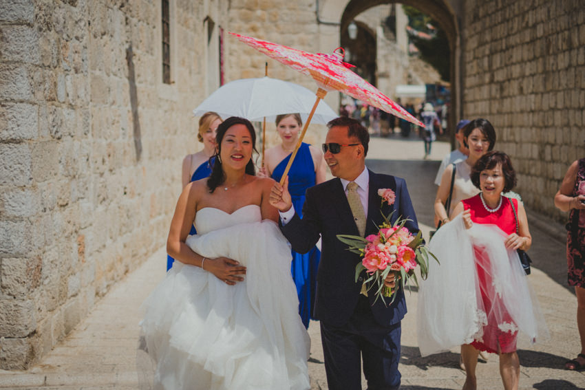 dad holding a parasol over the bride