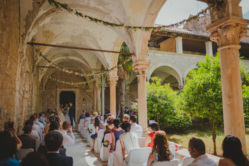 wide shot of the ceremony venue with guests and the newlyweds