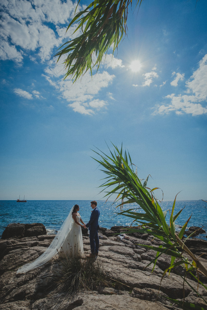bride and groom holding hands near the Adriatic sea
