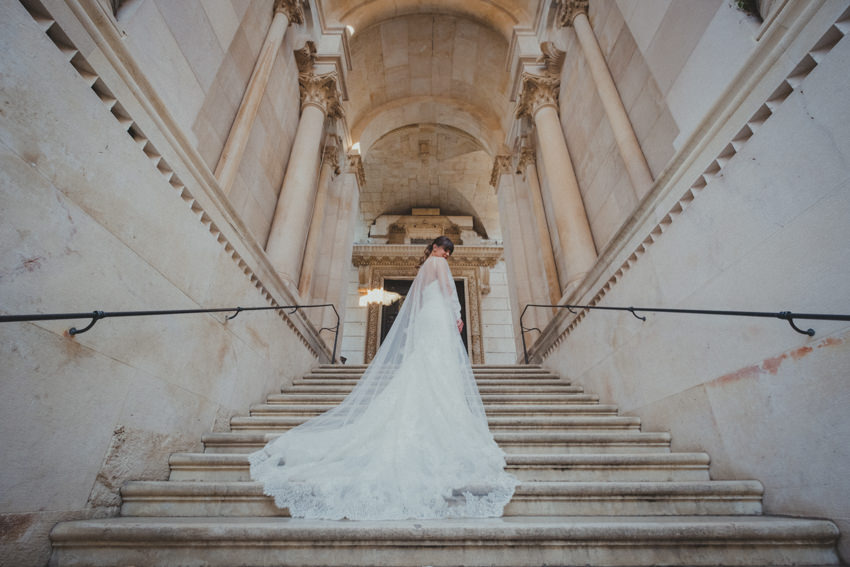 bride posing with weddingdress and train on the stairs of the cathedral
